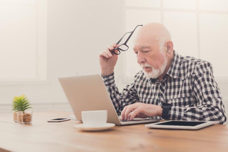 Hombre mayor preocupante que usa el ordenador portátil en casa foto de archivo