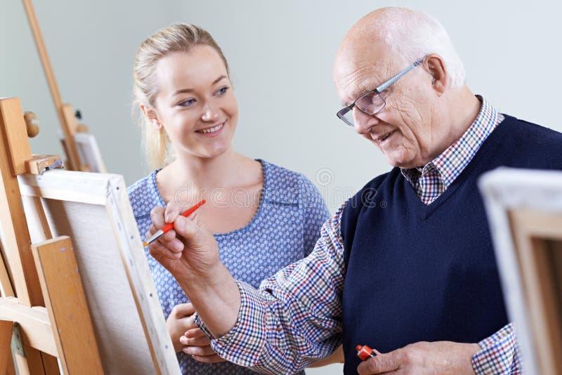 Hombre mayor que asiste a la clase de la pintura con el profesor imágenes de archivo libres de regalías