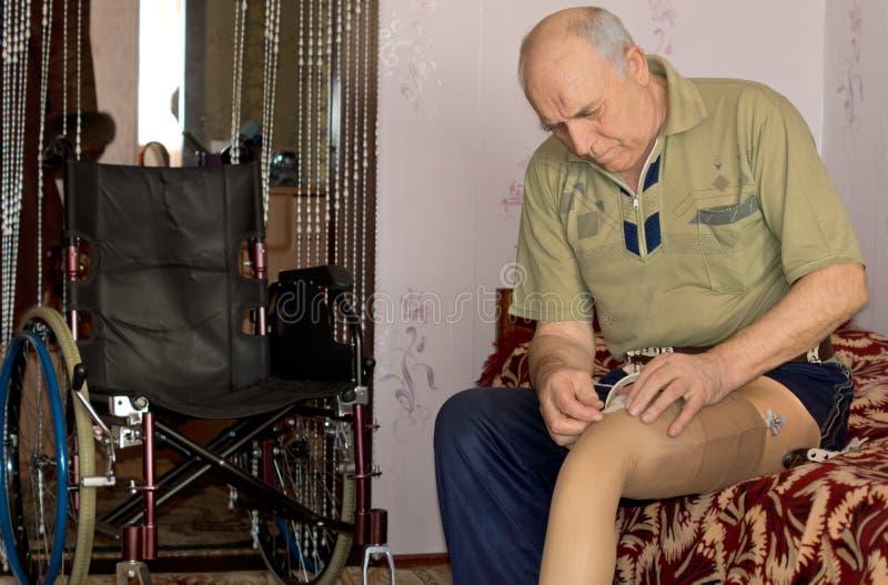 Hombre mayor que cabe su pierna prostética imagen de archivo libre de regalías