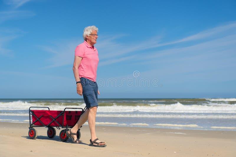Hombre mayor que camina con el carro rojo en la playa foto de archivo