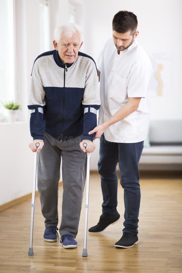 Hombre mayor que camina en las muletas y una enfermera de sexo masculino útil que lo apoya imagen de archivo libre de regalías