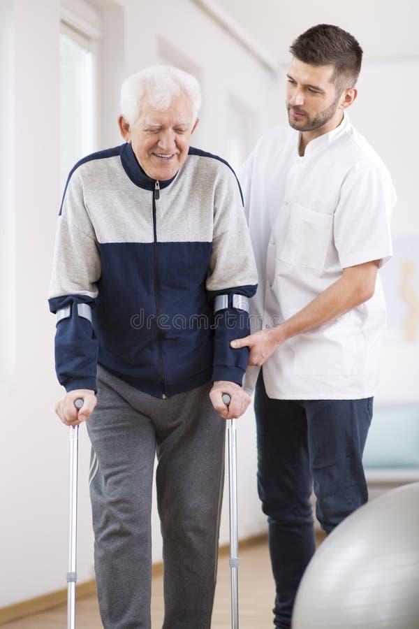 Hombre mayor que camina en las muletas y una enfermera de sexo masculino útil que lo apoya imagenes de archivo