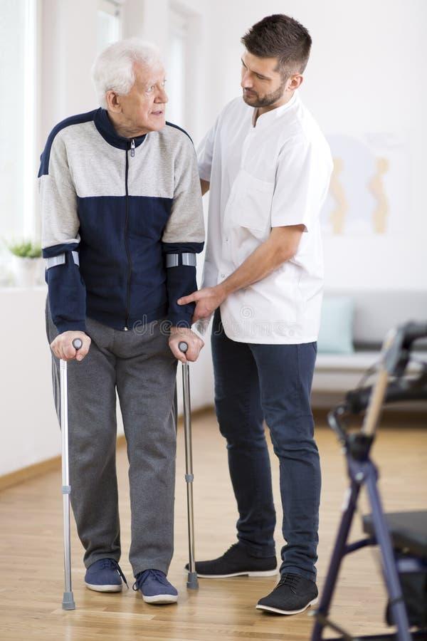 Hombre mayor que camina en las muletas y una enfermera de sexo masculino útil que lo apoya fotografía de archivo libre de regalías