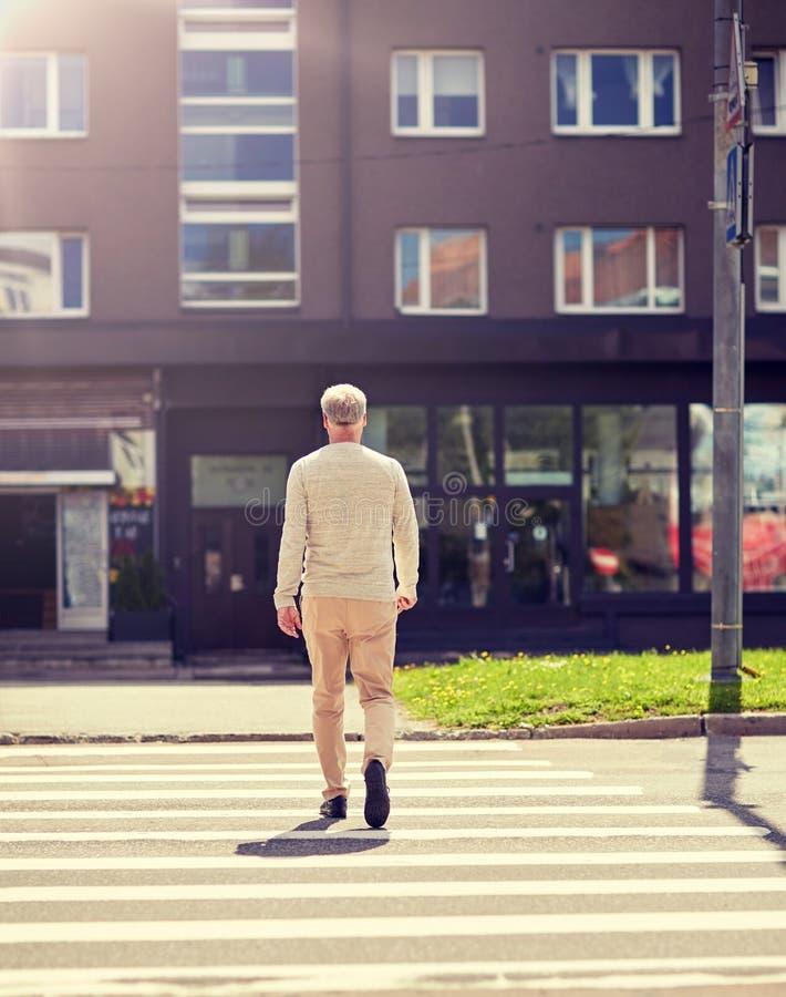 Hombre mayor que camina a lo largo de paso de peatones de la ciudad fotos de archivo libres de regalías