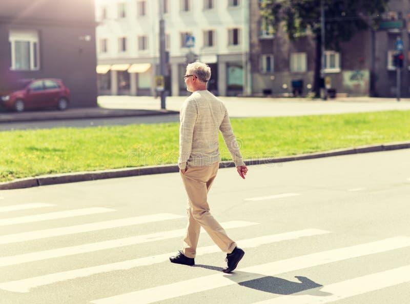 Hombre mayor que camina a lo largo de paso de peatones de la ciudad foto de archivo