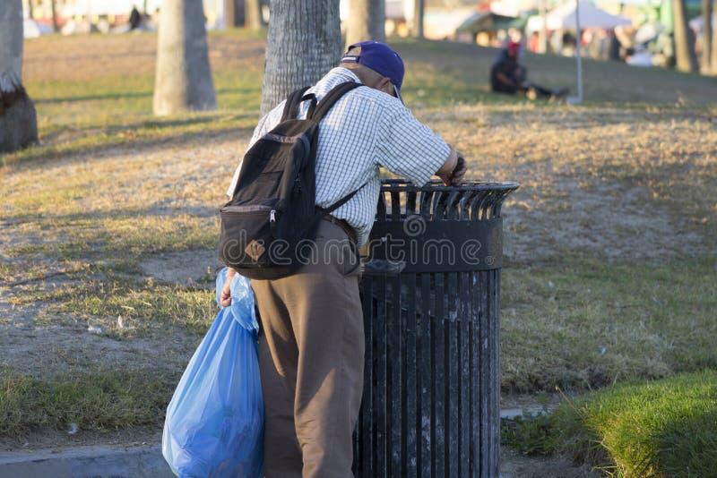 Hombre mayor que cava en basura fotografía de archivo