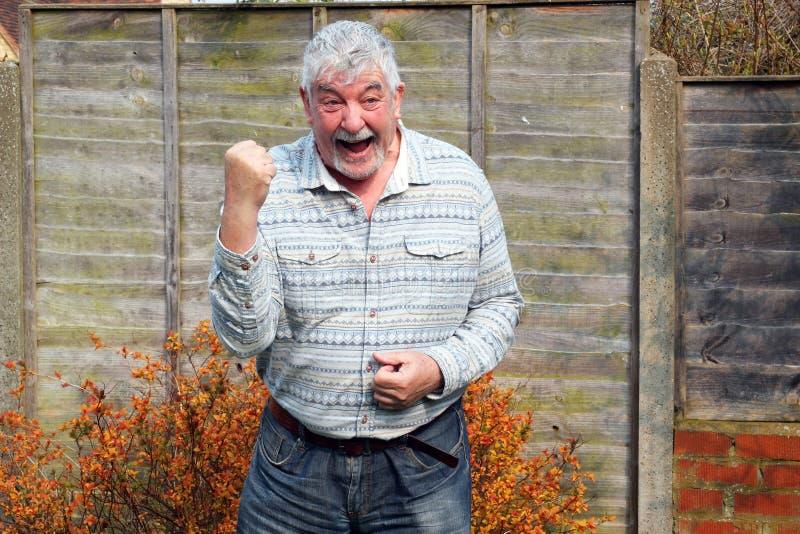 Hombre mayor que celebra su logro. imagenes de archivo