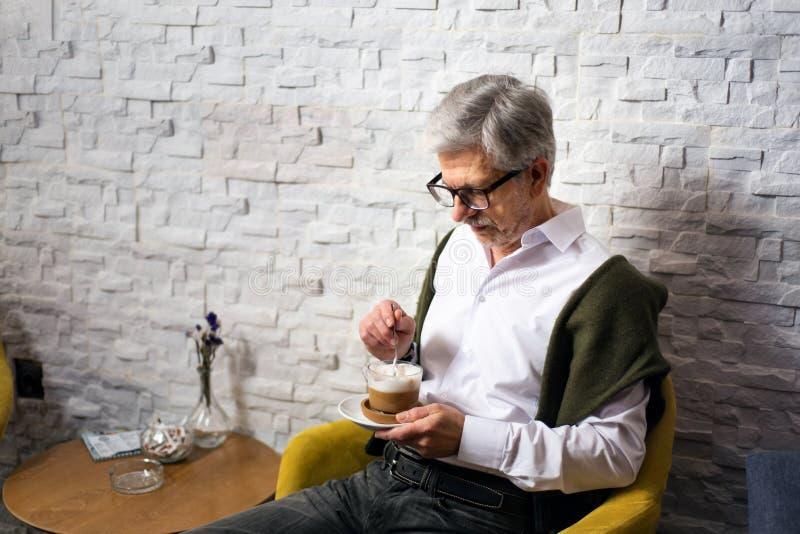 Hombre mayor que come un caf? en la barra imagen de archivo