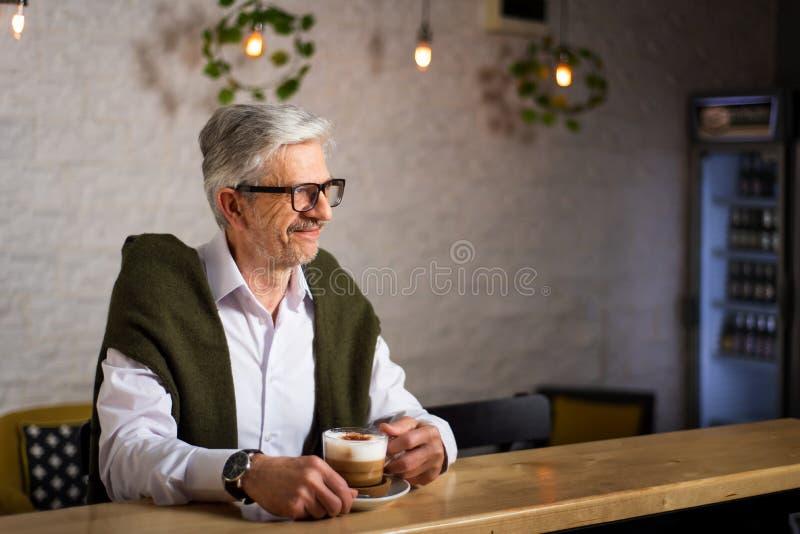 Hombre mayor que come un caf? en la barra fotos de archivo libres de regalías