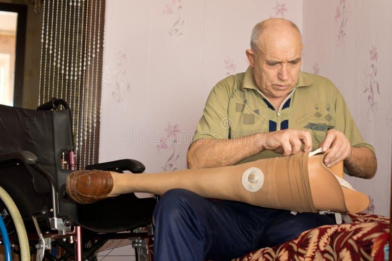 Hombre mayor que comprueba hacia fuera su pierna prostética imagen de archivo libre de regalías