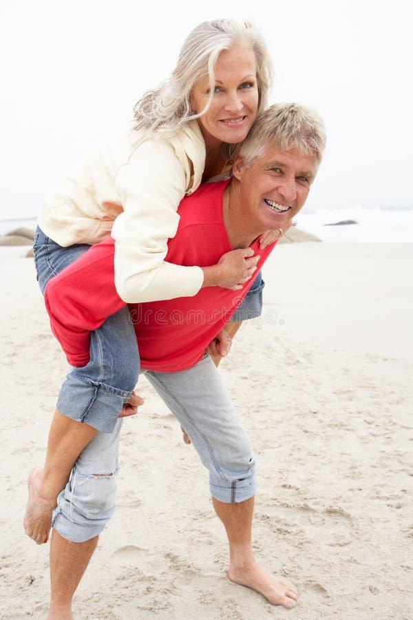 Hombre mayor que da de lengüeta de la mujer en la playa del invierno fotografía de archivo