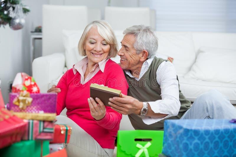 Hombre mayor que da el regalo de la Navidad a la mujer imágenes de archivo libres de regalías