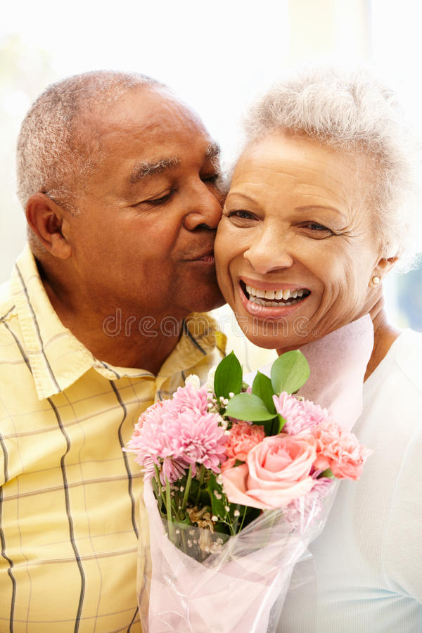 Hombre mayor que da las flores a la esposa foto de archivo libre de regalías
