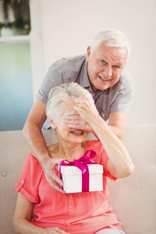Hombre mayor que da un regalo de la sorpresa a la mujer mayor fotos de archivo