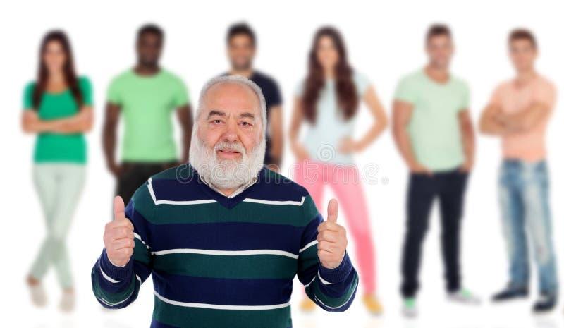 Hombre mayor que dice muy bien con la gente joven del fondo fotos de archivo