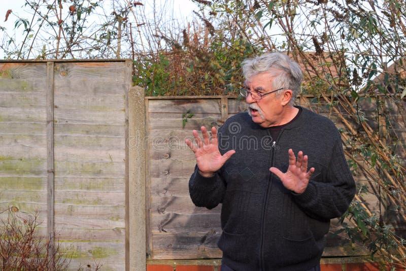Hombre mayor que dice no o parada con las manos aumentadas. imagenes de archivo