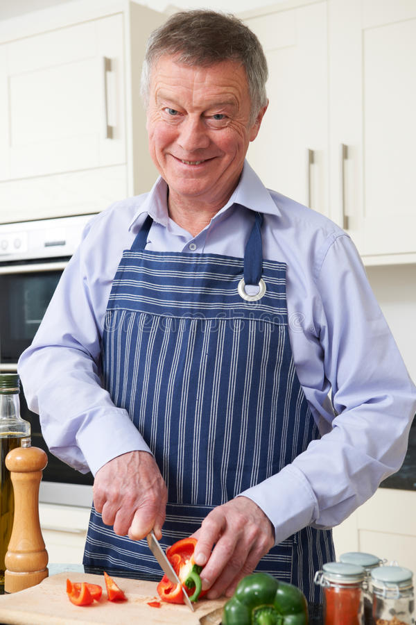 Hombre mayor que disfruta de cocinar en cocina foto de archivo
