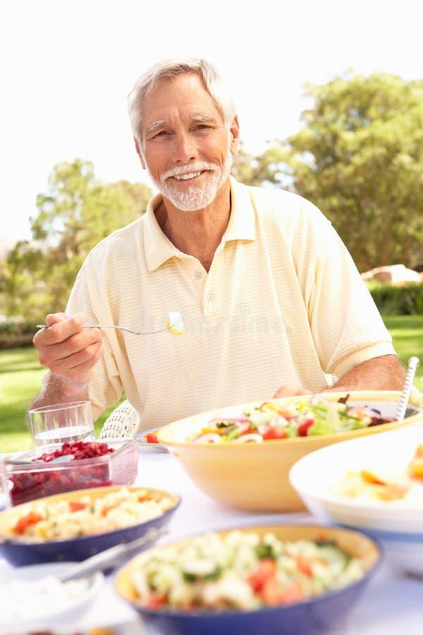 Hombre mayor que disfruta de la comida en jardín imagenes de archivo