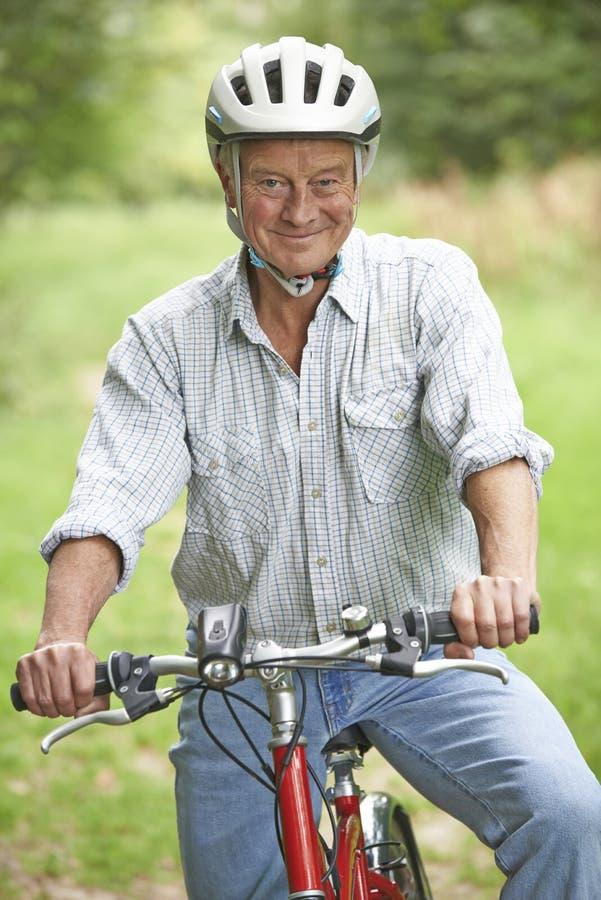 Hombre mayor que disfruta de paseo del ciclo en el campo fotografía de archivo