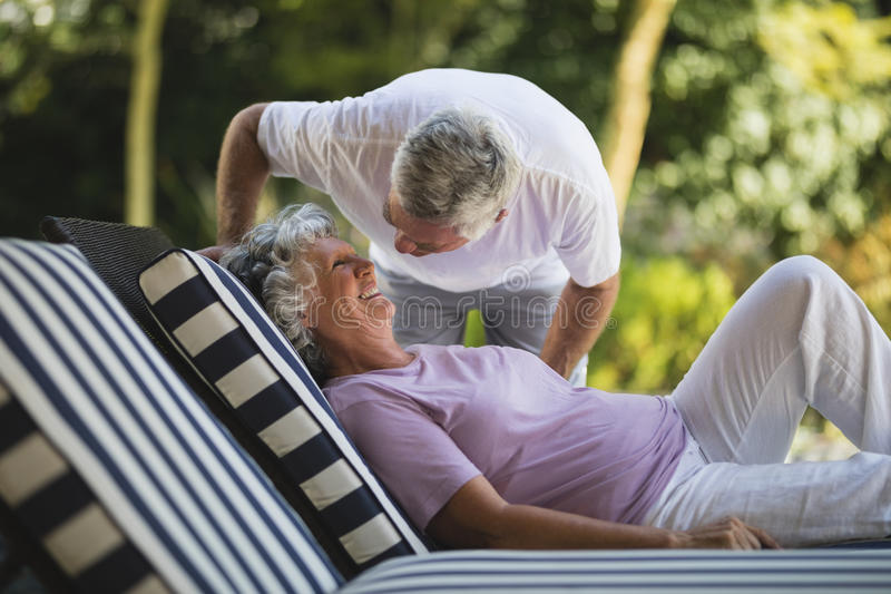 Hombre mayor que dobla sobre la mujer que descansa sobre sillón foto de archivo libre de regalías