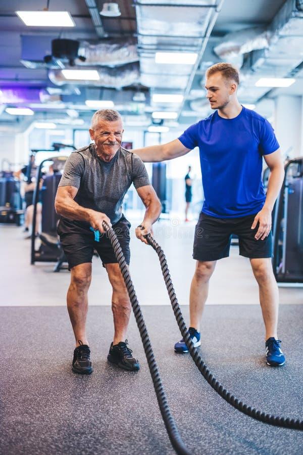 Hombre mayor que ejercita en el gimnasio con el instructor de gimnasio imagen de archivo libre de regalías