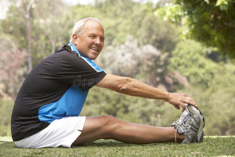 Hombre mayor que ejercita en parque imagen de archivo libre de regalías