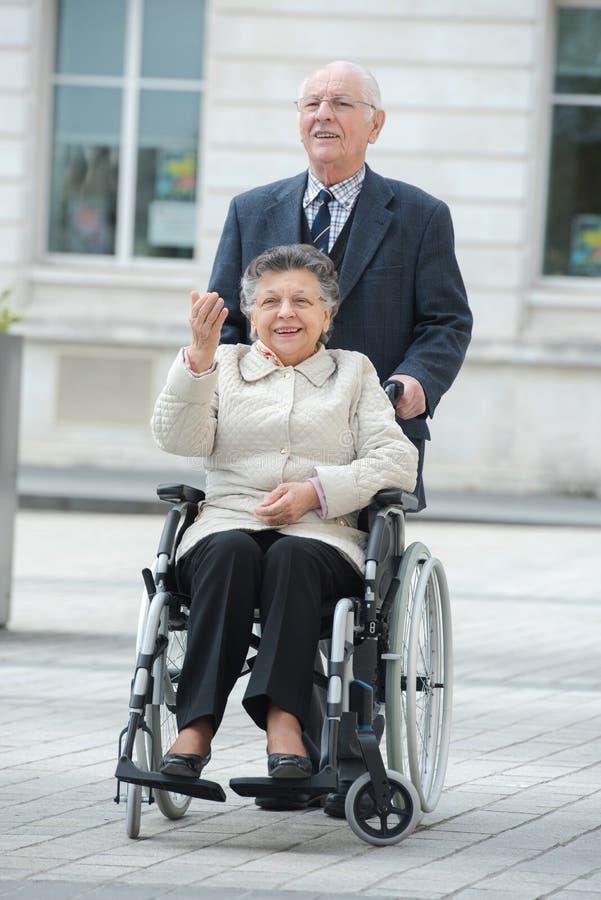 Hombre mayor que empuja a la mujer en silla de ruedas en ciudad imagen de archivo libre de regalías