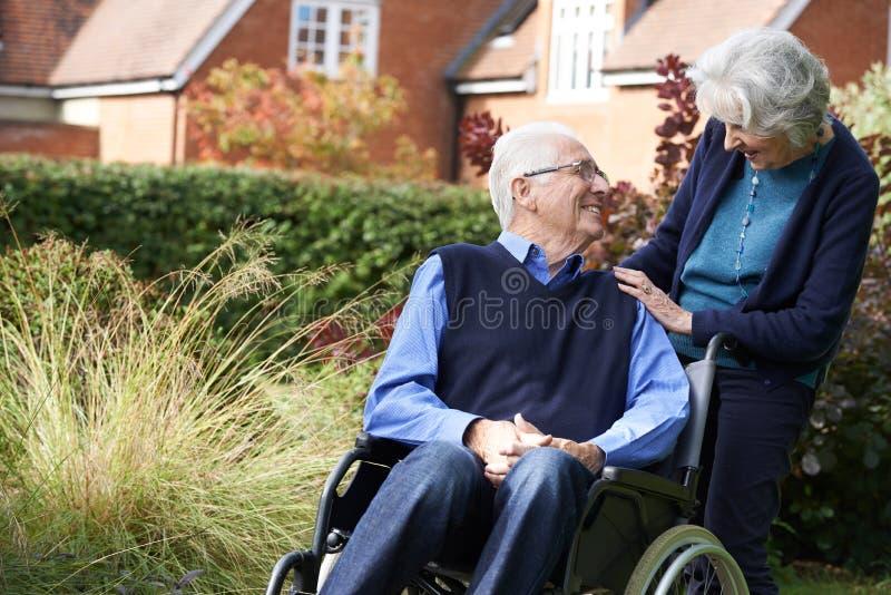 Hombre mayor que es empujado hacia adentro silla de ruedas por la esposa foto de archivo libre de regalías