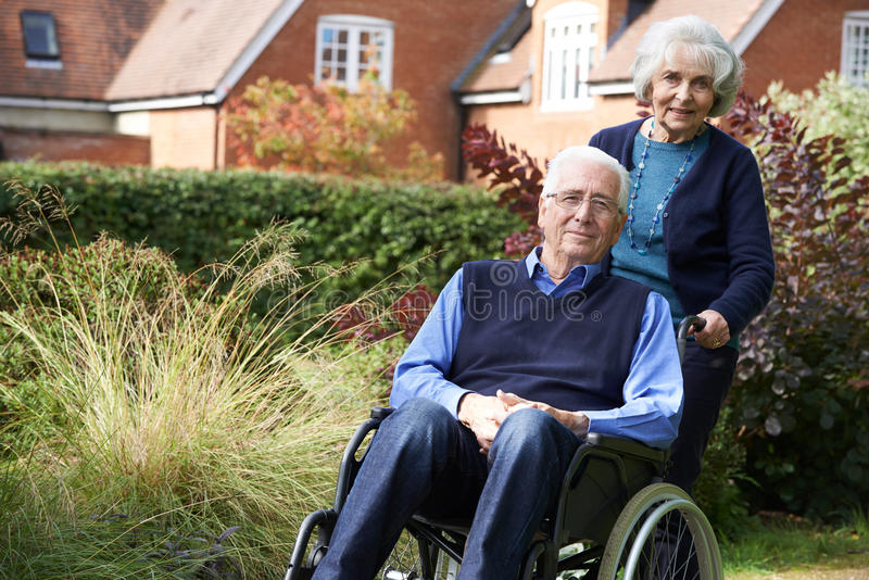 Hombre mayor que es empujado por la esposa en silla de ruedas foto de archivo