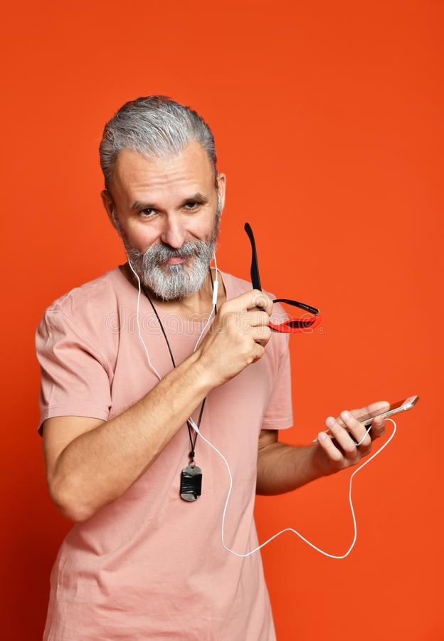Hombre mayor que escucha la música en los auriculares aislados en fondo anaranjado imágenes de archivo libres de regalías