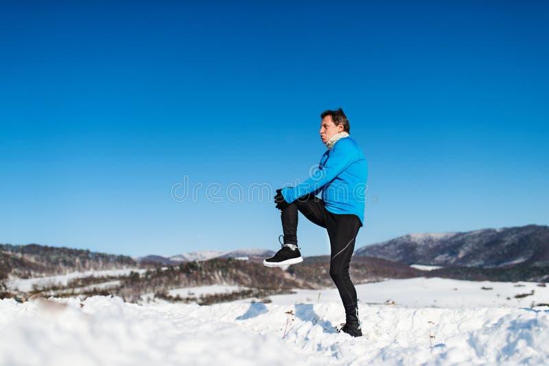 Hombre mayor que estira antes del funcionamiento en naturaleza del invierno Copie el espacio fotos de archivo