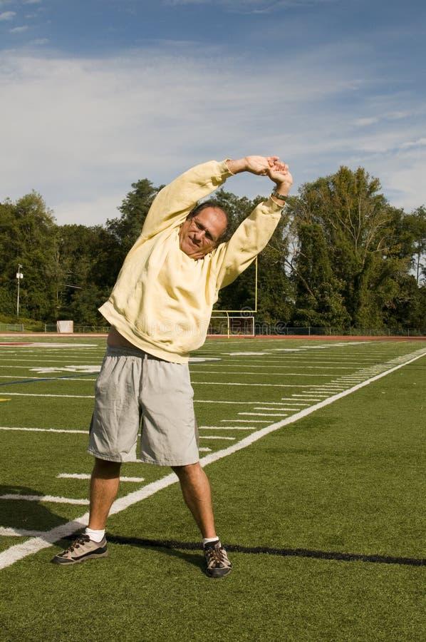 Hombre mayor que estira ejercitando el campo de deportes imagen de archivo
