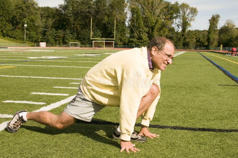 Hombre mayor que estira el ejercicio en campo de deportes foto de archivo libre de regalías