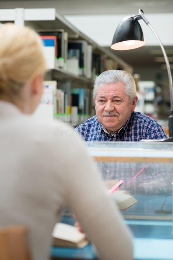 Hombre mayor que estudia entre gente joven en biblioteca imagen de archivo libre de regalías