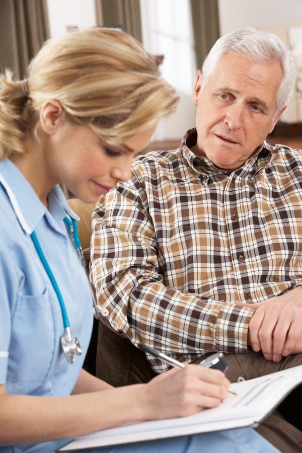 Hombre mayor que habla con el visitante de la salud foto de archivo