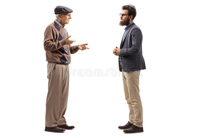 Hombre mayor que habla con un hombre barbudo más joven imagen de archivo libre de regalías