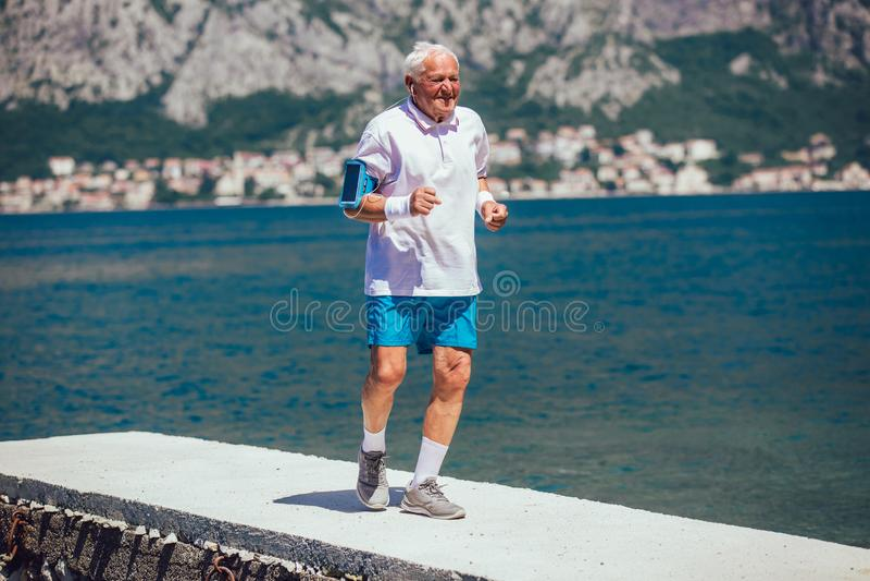 Hombre mayor que hace ejercicio de la mañana en la playa fotos de archivo