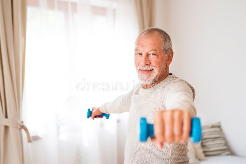 Hombre mayor que hace ejercicio en casa foto de archivo