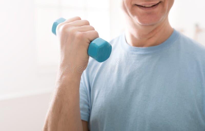 Hombre mayor que hace el ejercicio para el bíceps con pesas de gimnasia foto de archivo libre de regalías