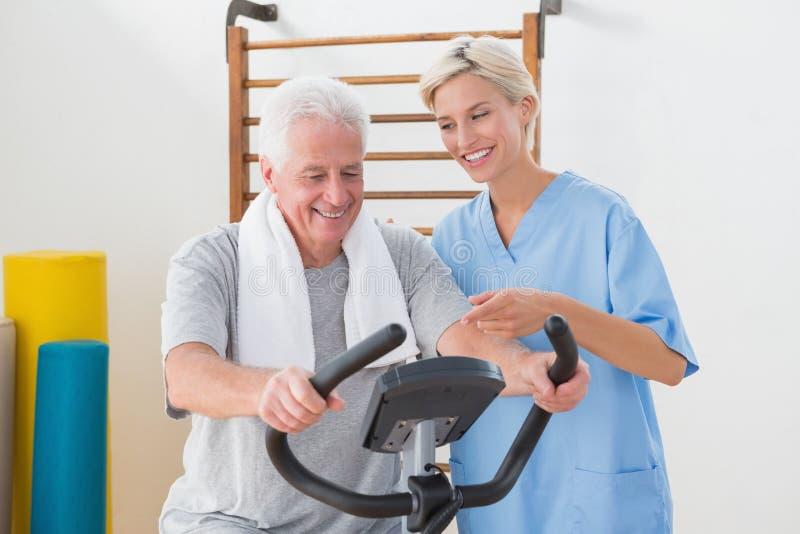 Hombre mayor que hace la bicicleta estática con el terapeuta imagen de archivo