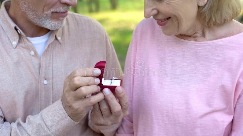 Hombre mayor que hace propuesta de matrimonio a la señora, fechando los sitios para la gente de anciano foto de archivo libre de regalías