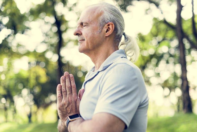 Hombre mayor que hace yoga en el parque imágenes de archivo libres de regalías