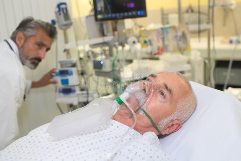 Hombre mayor que inhala a través de máscara de oxígeno en clínica fotografía de archivo libre de regalías