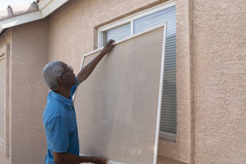 Hombre mayor que instala una pantalla de la ventana foto de archivo libre de regalías