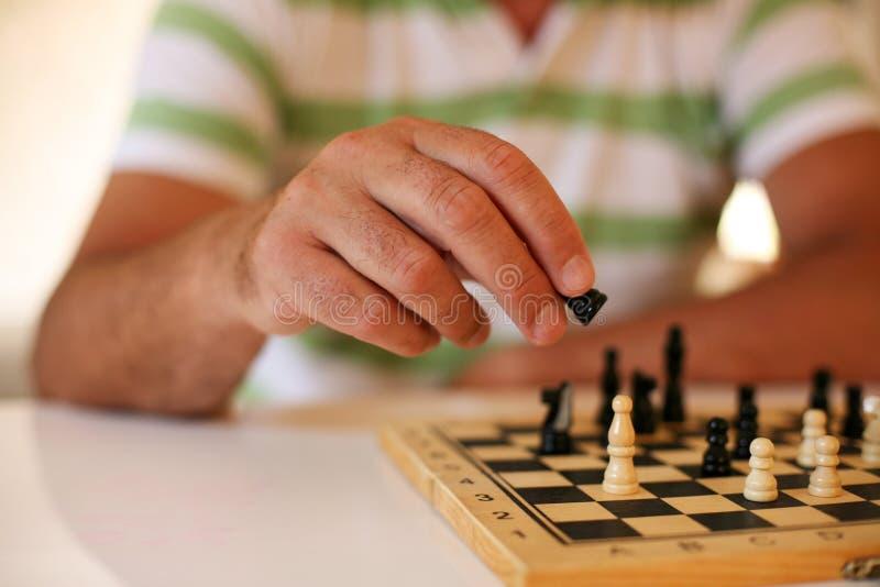 Hombre mayor que juega al ajedrez, primer de la mano fotografía de archivo libre de regalías