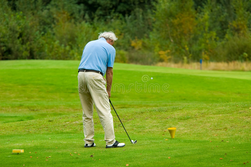 Hombre mayor que juega a golf foto de archivo