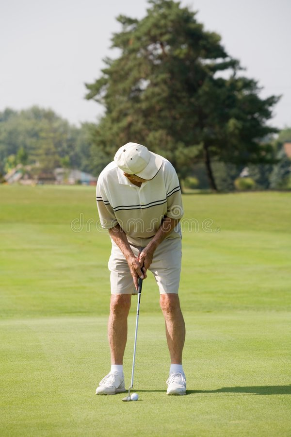 Hombre mayor que juega a golf fotografía de archivo libre de regalías