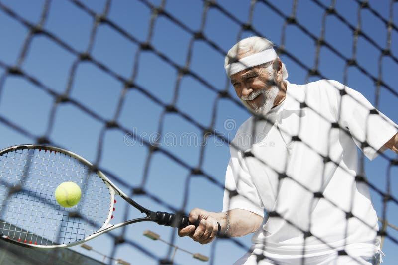 Hombre mayor que juega a tenis foto de archivo
