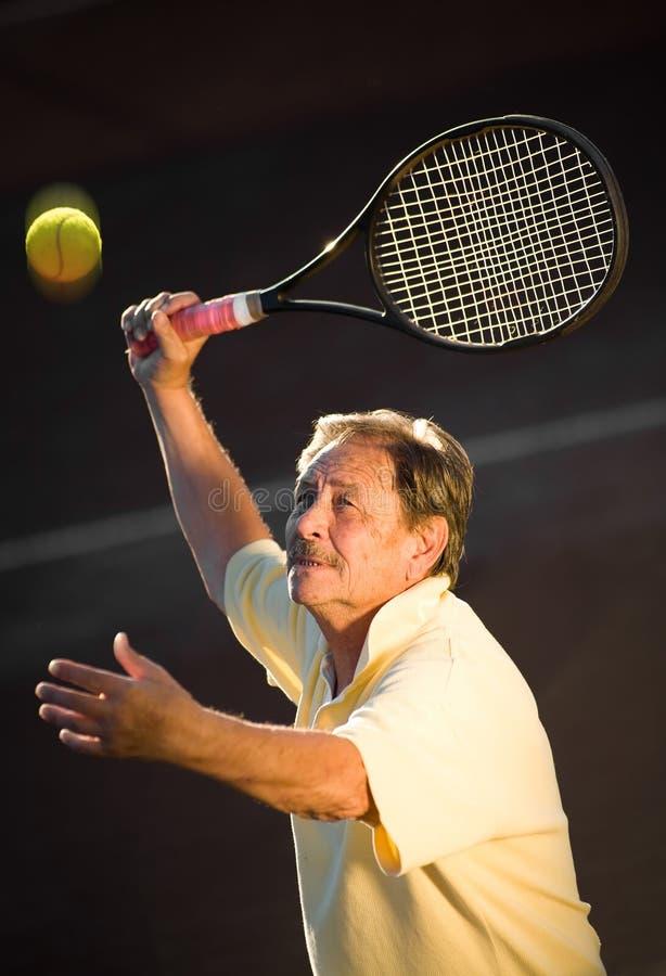 Hombre mayor que juega a tenis imagenes de archivo