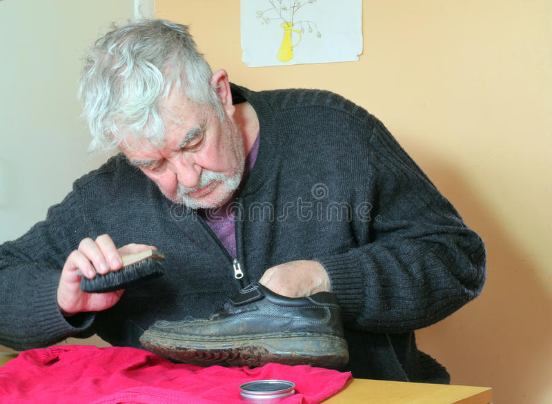 Hombre mayor que limpia sus zapatos fotografía de archivo